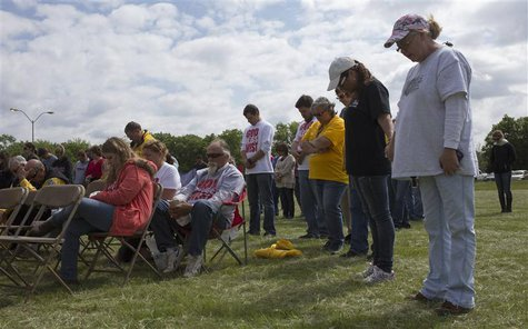 Church goers bow their heads in prayer during an open air Sunday service four days after a deadly fertilizer plant explosion in the town of