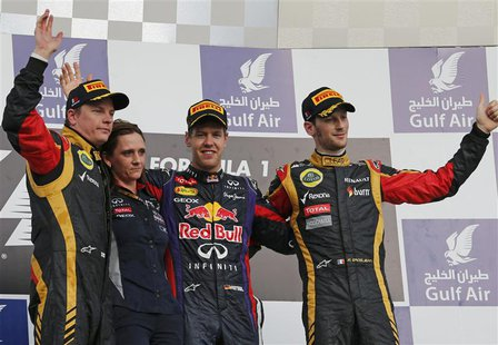 First placed Red Bull Formula One driver Sebastian Vettel of Germany (2nd R), second placed Lotus Formula One driver Kimi Raikkonen of Finla