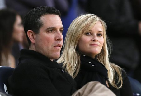 Actress Reese Witherspoon (R) and her husband Jim Toth watch the Toronto Raptors play the Los Angeles Lakers in their NBA basketball game in