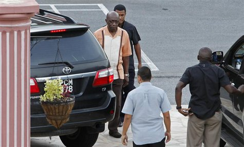 Trinidad and Tobago's National Security Minister Jack Warner leaves with bodyguards after an emergency cabinet meeting at the private reside