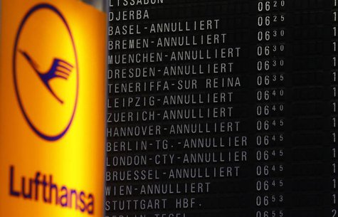Cancelled flights are seen on a flight schedule board next to the logo of German air carrier Lufthansa at the Fraport airport in Frankfurt,