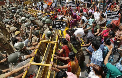 Police try to stop supporters of India's main opposition Bharatiya Janata Party (BJP) as they march towards the residence of the chief of In
