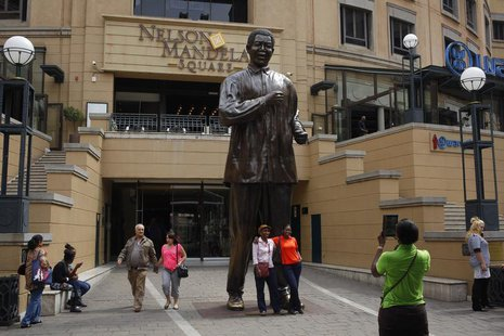 Visitors pose for photographs in front of a statue of former South African president Nelson Mandela in Sandton, Johannesburg March 30, 2013.