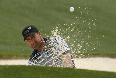Former champion Jose Maria Olazabal of Spain hits from a sand trap on the 18th green during first round play in the 2013 Masters golf tourna