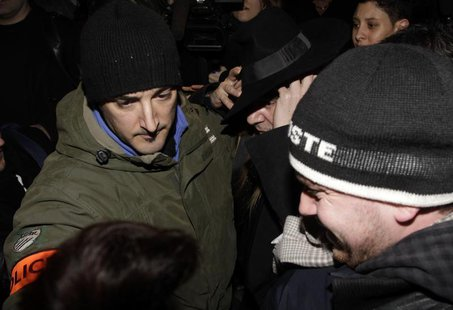 Fashion designer John Galliano surrounded by policemen leaves after a hearing in a police station in Paris February 28, 2011. REUTERS/Jacky
