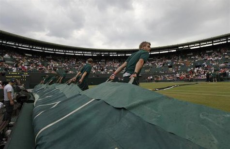 The covers are pulled over number one court as rain stops play in the match between Fernando Verdasco of Spain and Ivo Karlovic of Croatia a