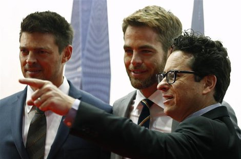 Actors Karl Urban (L) and Chris Pine (C) look on as director J.J. Abrams points to a camera at the red carpet of the Australian premiere of