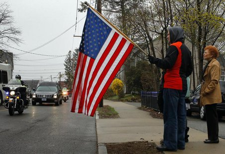Richard Corapi holds a U.S. flag from a sidewalk while the hearse carrying the body of Massachusetts Institute of Technology (MIT) police of