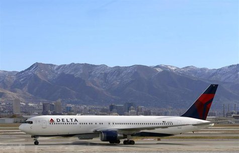 A Delta Airlines Boeing 767 passenger jet taxis past the Salt Lake City skyline, a day before the annual Thanksgiving Day holiday, at the Sa