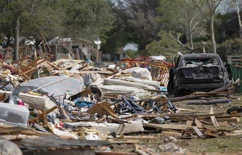 Debris from a destroyed housing complex lies near a damaged vehicle, next to the site of a deadly fertilizer plant explosion in the town of