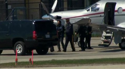 Canadian police escort suspect Chiheb Esseghaier from a plane to a truck after arriving in Markham, Ontario, April 22, 2013, in this still i