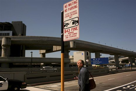 An airline passenger waits at a curb at San Francisco International Airport in San Francisco, California April 22, 2013. REUTERS/Robert Galb