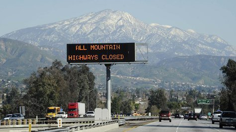 A sign near the San Bernardino Mountains warns of road closures during a manhunt for former LAPD officer Christopher Dorner, wanted in conne