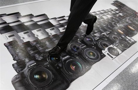 A man walks on an advertisement of Canon digital cameras at an electronics retail store in Tokyo April 23, 2013. Japan's Canon Inc said firs