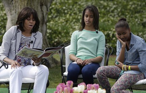 "U.S. first lady Michelle Obama (L-R) reads the children's book ""Cloudy with a Chance of Meatballs"" as her daughters Malia and Sasha look on,"