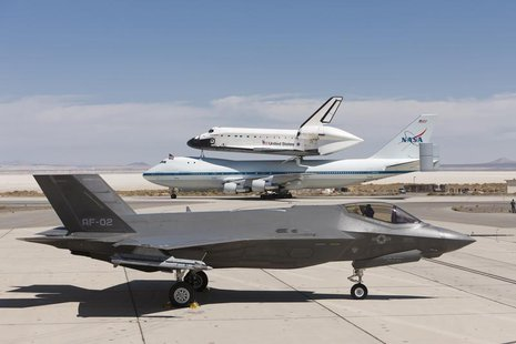 A Lockheed Martin F-35 Joint Strike Fighter (JSF) is pictured with the space shuttle Endeavour mounted atop its 747 Shuttle Carrier Aircraft