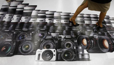 A woman walks on an advertisement for Canon digital cameras at an electronics retail store in Tokyo April 23, 2013. REUTERS/Toru Hanai