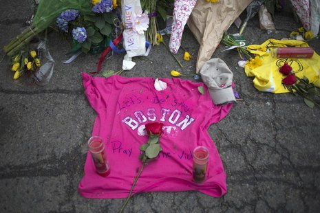 Well-wishers leave a shirt at a make-shift memorial on Boylston Street a day after two explosions hit the Boston Marathon in Boston, Massach