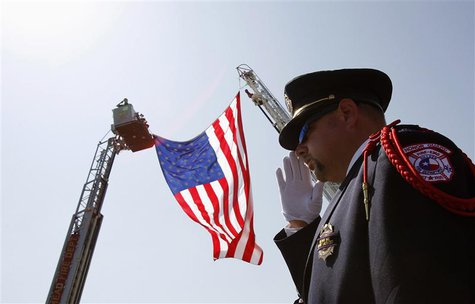 "Killeen, Texas, fire-fighter Charles Layton salutes a procession of vehicles in honor of fallen fire-fighter Captain Kenneth ""Luckey"" Harris"