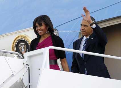 U.S. President Barack Obama waves next to first lady Michelle Obama as they arrive in Dallas April 24, 2013. REUTERS/Jason Reed