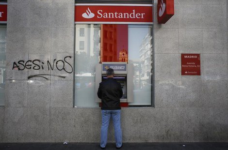 A man uses an ATM machine at a Santander bank branch in Madrid April 23, 2013. REUTERS/Susana Vera