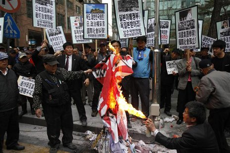 "A South Korean conservative right-wing protester burns a Japanese ""rising sun"" flag as they chant slogans during an anti-Japan rally in fron"