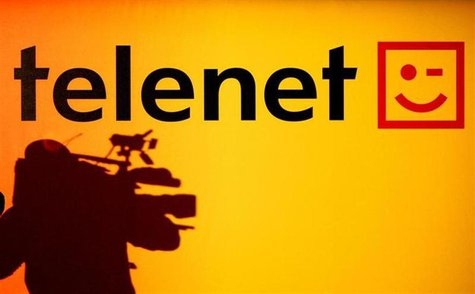 The shadow of a cameraman is seen beside the Belgian cable operator Telenet logo during a news conference in Brussels. REUTERS/Thierry Roge