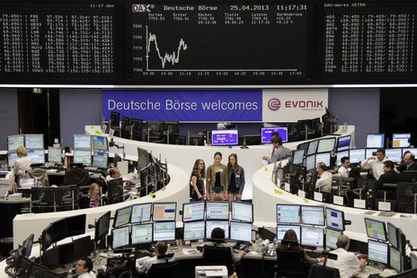Traders work at their desks in front of the DAX board, as visitors pose for a picture at the Frankfurt stock exchange April 25, 2013. REUTER