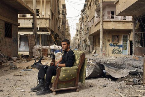 A member of the Free Syrian Army holds his weapon as he sits on a sofa in the middle of a street in Deir al-Zor, in this April 2, 2013 file