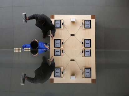 A visitor talks with a staff member at an Apple store in Beijing April 2, 2013. REUTERS/Kim Kyung-Hoon