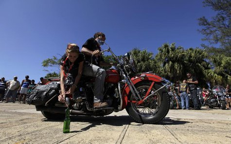 A man and a woman take part in a competition of riding skills in their Harley Davidson motorcycle during Cuba's Second Harley Davidson Conve