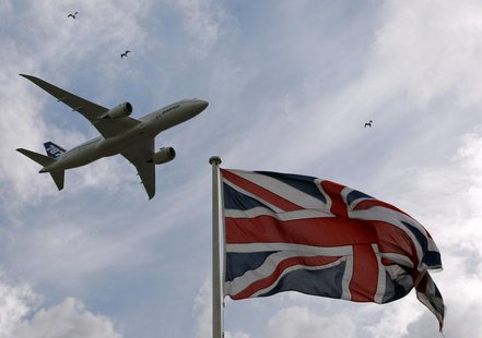 A Boeing 787 Dreamliner aircraft flies over a Union flag as it makes a salute to its engine makers Rolls-Royce in Derby, central England Jul
