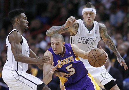 Miami Heat's Norris Cole (L) defends against Los Angeles Lakers' Steve Blake (C) as Heat teammate Chris Andersen (R) looks on in the first h