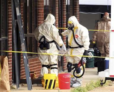 Hazmat officers enter a taekwondo studio previously operated by James Everett Dutschke in Tupelo, Mississippi April 24, 2013. REUTERS/Lauren