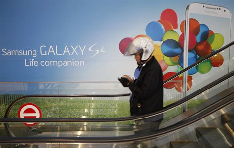A motorcycle dispatch rider uses his smartphone next to an advertisement promoting Samsung Electronics Co Ltd's latest flagship smartphone G