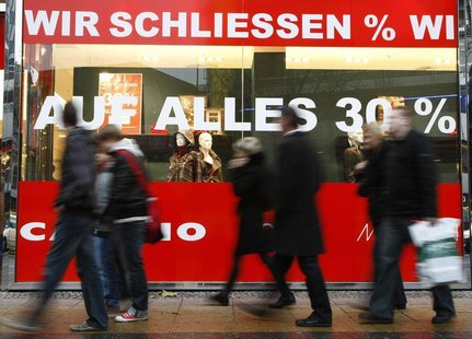 People pass by a clothes shop which will be closed with advertising banners reading 'We are closing, 30% on all' at Berlin's Kurfuerstendamm