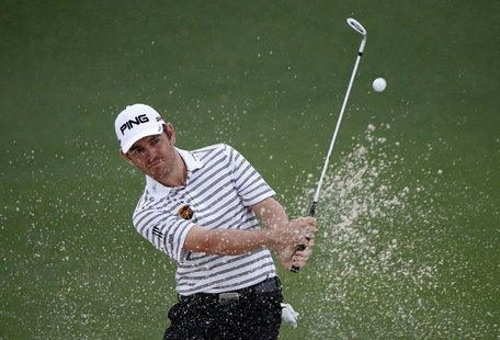 Louis Oosthuizen of South Africa hits from a sand trap on the second hole during second round play in the 2013 Masters golf tournament at th