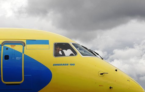 A crew member sits in the cockpit as an Embraer 190 is guided onto its stand ahead of the Farnborough Airshow 2012 in southern England July