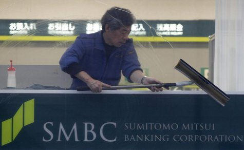 A man cleans up a window at a branch of Sumitomo Mitsui Banking Corporation in Tokyo January 29, 2013. REUTERS/Shohei Miyano