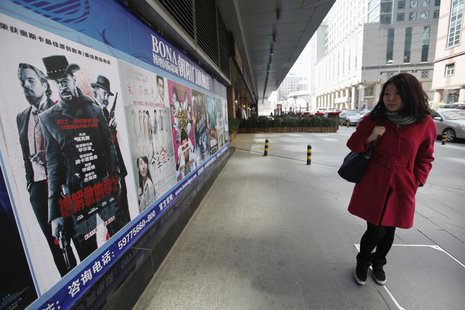 "A woman looks at a poster of the film ""Django Unchained"" outside a cinema in Beijing, April 11, 2013. REUTERS/Jason Lee"