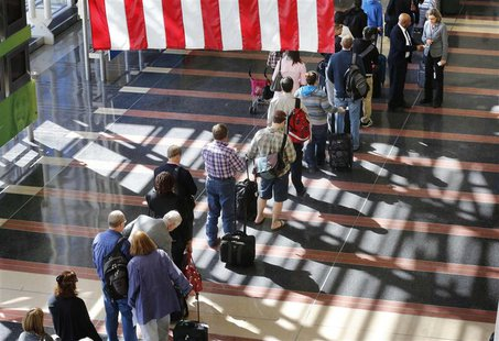 A long line of passengers wait to enter the security checkpoint before boarding their aircraft at Reagan National Airport in Washington, Apr