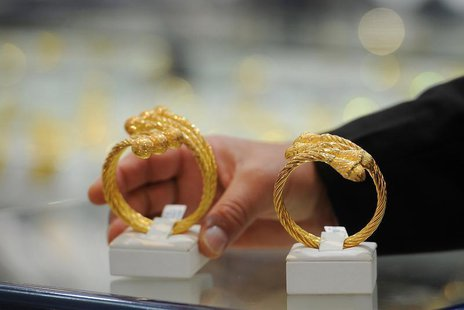 A woman looks at jewellery in a gold shop at Hamdan street in Abu Dhabi April 23, 2013. REUTERS/Ben Job