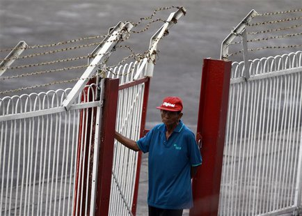 A security personnel wears a cap bearing the brand of Digicel as he mans a gate at a soccer match at Aung San stadium in Yangon April 26, 20