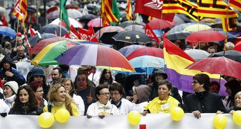 People hold umbrellas as they march with a banner during a protest against government austerity measures in Barcelona April 28, 2013. REUTER