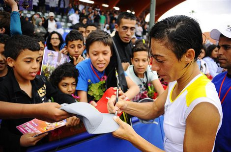 Francesca Schiavone of Italy signs autographs for fans after defeating Lourdes Dominguez Lino of Spain in their women's singles final tennis