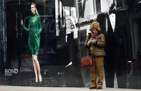 A woman looks at her mobile phone as she stands on New Bond Street in London April 19, 2013. REUTERS/Suzanne Plunkett