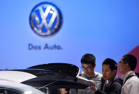 Guests look at a Volkswagen car during the media day at 15th Shanghai International Automobile Industry Exhibition in Shanghai April 20, 201