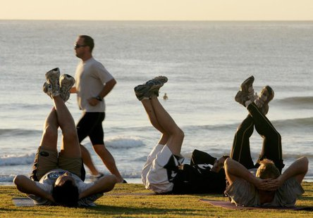 A jogger (2nd L) passes fitness enthusiasts performing stretching exercises after sunrise at Queenscliff Beach in Sydney on the first day of
