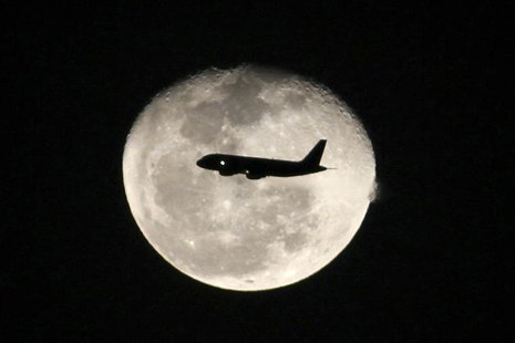 A passenger jet flies in front of the moon in Bogota November 1,2012. REUTERS/Felipe Caicedo