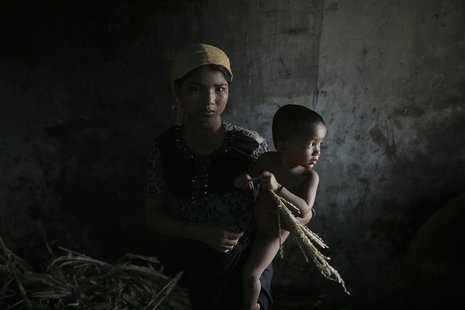 Hla Hla May, a Rohingya Muslim woman displaced by violence, holds her one year old daughter Roshan at a former rubber factory that now serve